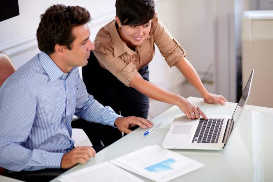 Portrait of two professional colleagues looking at computer while talking on workplace