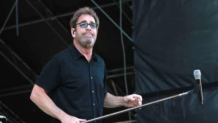 huey lewis holding microphone on stage