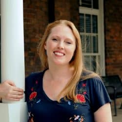 Ashley Shew standing on porch with arm around pillar smiling