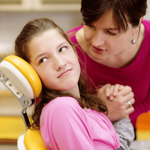 Child sitting in dental chair tightly gripping mother's hand