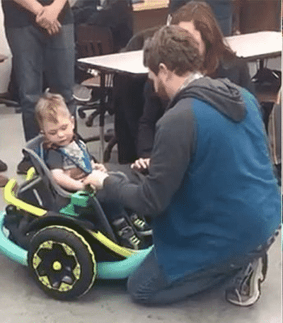 Rogue Robotics team member attends to the wheelchair that the little boy is sitting in