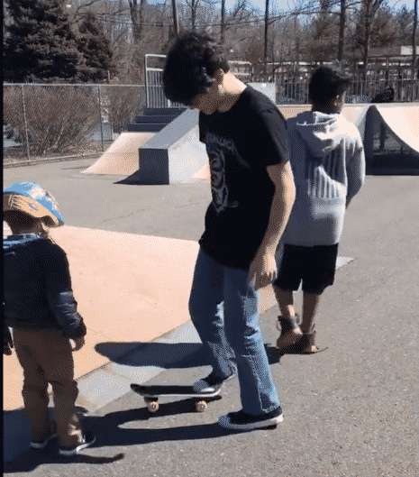 Teens at skatepark showing an autistic five year old boy with his helmet on how to skateboard