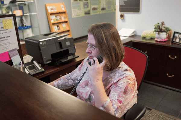Renae Templeton is sitting at work desk talking on the phone and on the computer