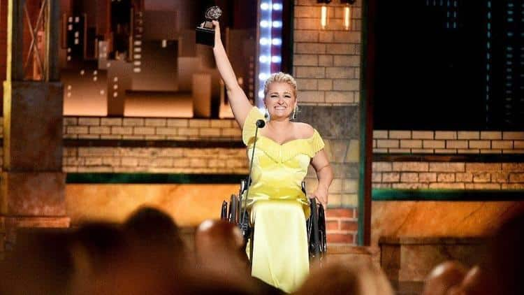 Ali Stoker is sitting in a wheelchair in a yellow evening dress holding her award atatue in the air with her right hand with a huge smile