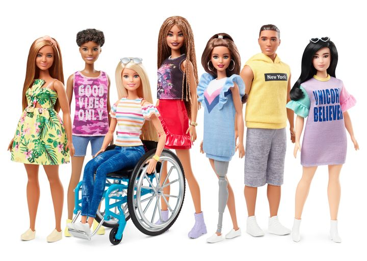 Barbie sittin in a wheelchair is with her group of doll friends