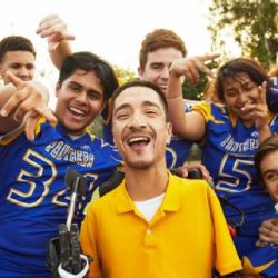 Rob Mendez poses with group of high school football team