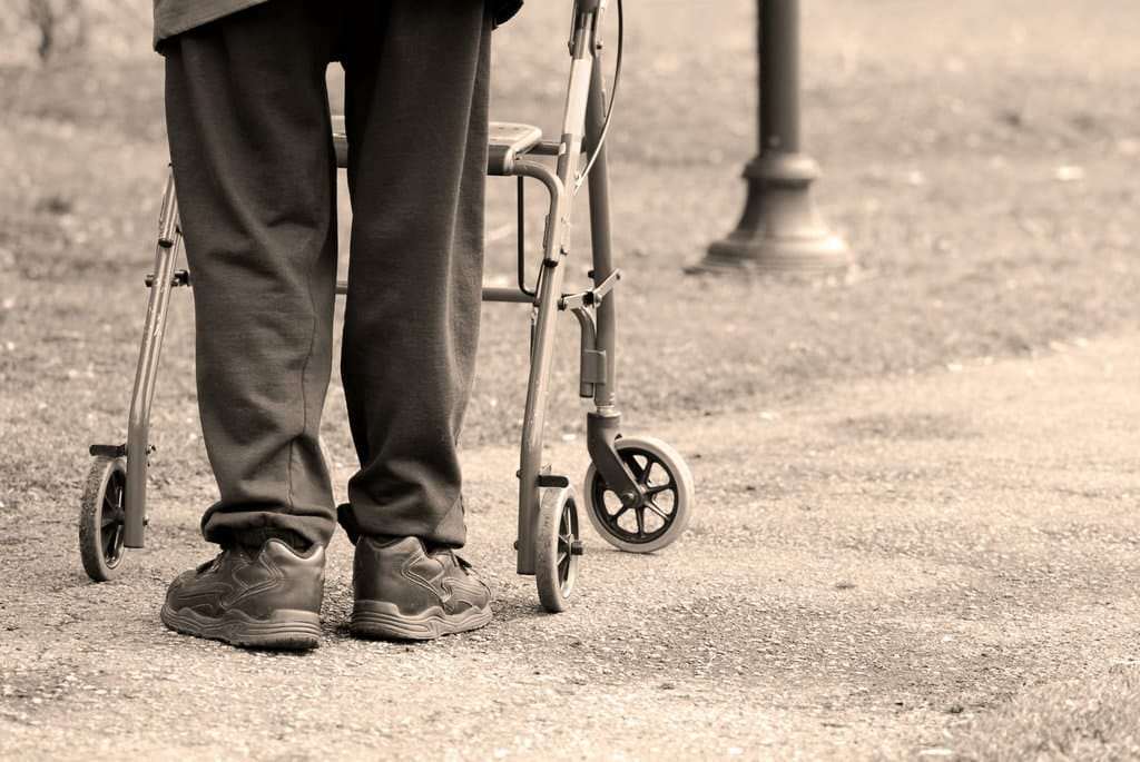 man walking outside using a walker