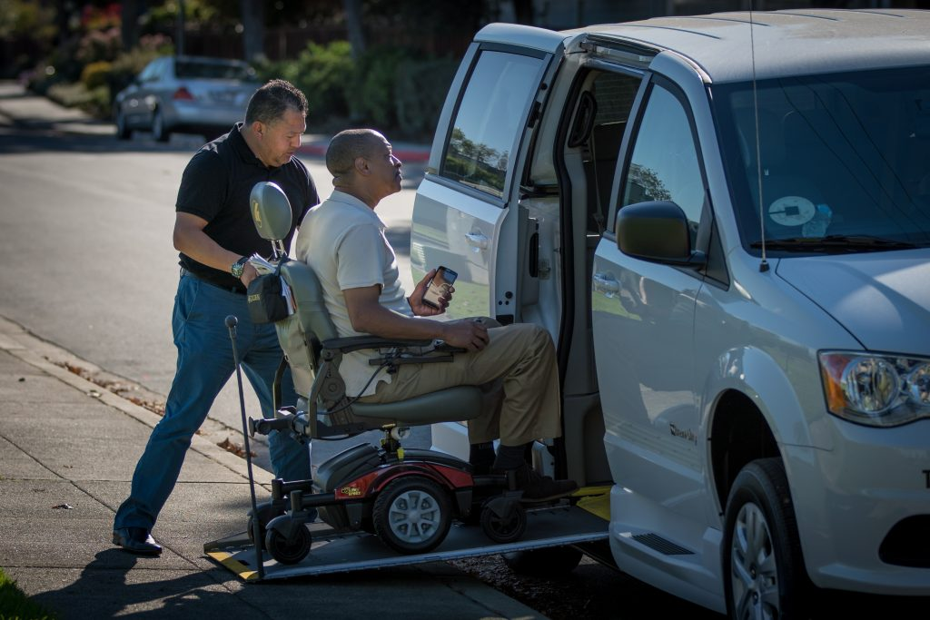 BER driver assisting man in a wheelchair