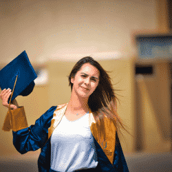 female grad student wearing her graduate robe and holding cap in her hand