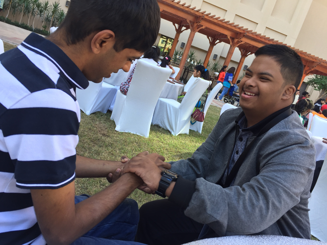 two young men seated on the grass shaking hands and smiling