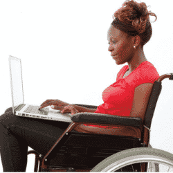 women in wheelchair looking at laptop held in her lap