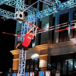 Brian Burke swing across obstacle course on Ninja Warrior stage