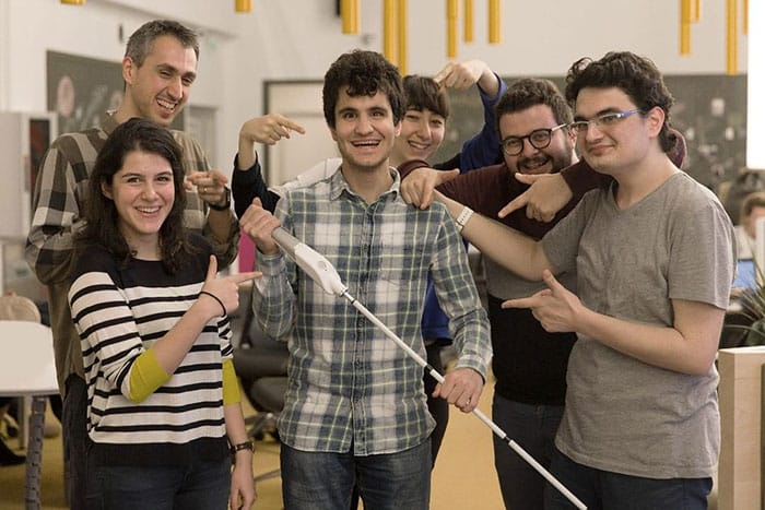 Blind engineer poses with his smart cane and a group of people smiling and pointing to him
