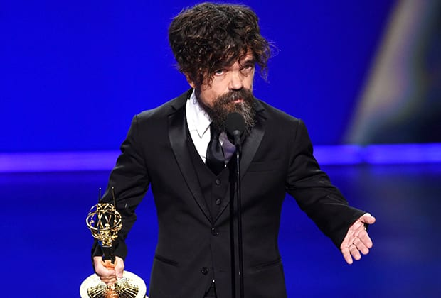 Peter Dinklage onstage behind podium holding his eEmmy while speaking to audience