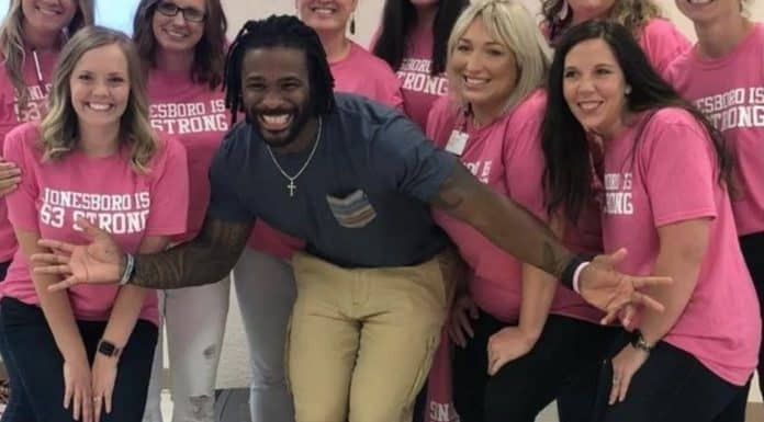 DeAngelo Williams pictured with many women posing in pink t-shirts for the Breast Cancer Pink Camp