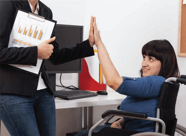 women sitting in a wheelchair at work giving a high-five to a coworker