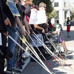 several people pictured holding out their white canes on the sidewalk