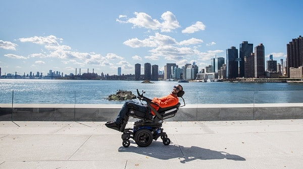Man sitting on a boardwalk in a tilt and recline position in his wheelchair with the beach in the background