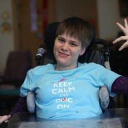 Erin Feeney is smiling and giving a hand signal that all is good while seated in here chair at home