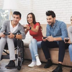 Two guys and two girls play on the game console. One of the guys is disabled in a wheelchair.