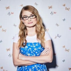 Kayla Cromer is standing in front of a background with colorful butterflies wearing a bright blue floral dress