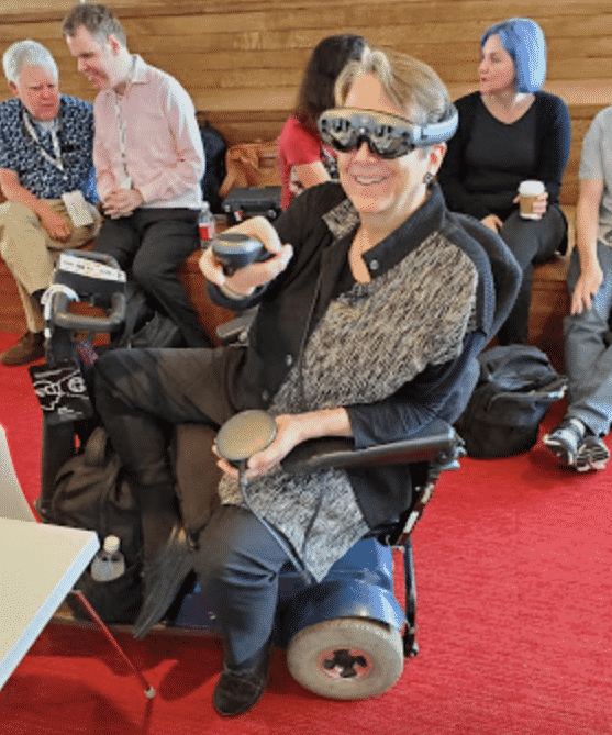 Women in wheelchair at the access symposium wearing the Oculus headgear