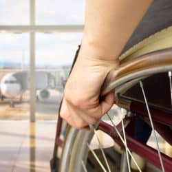 rear view of a man in wheelchair at the airport with focus on hand