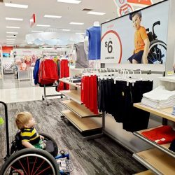 Young child sitting in wheelchair in Target stops to see advertisement of a young boy in a wheelchair