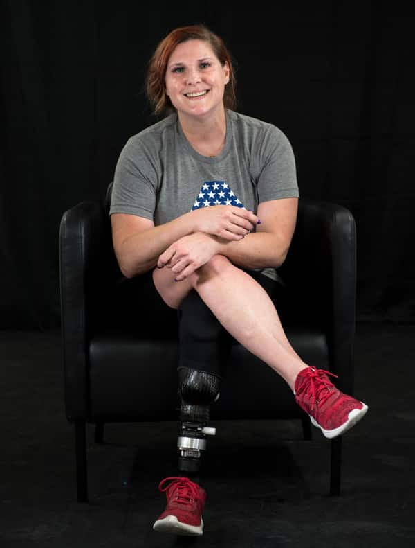 Lee wearing her prosthetic leg and smiling sitting on a chair with legs crossed in workout attire