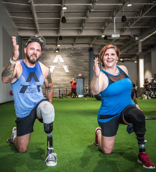 Lee and partner kneeling and smiling with arms raised during a workout at the gym