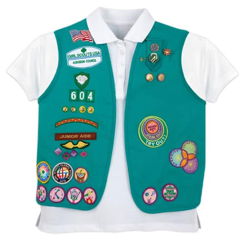Girl Scouts green vest, white shirt beneath, with many badges