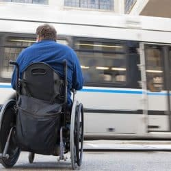 man in a wheelchair outside waiting for train