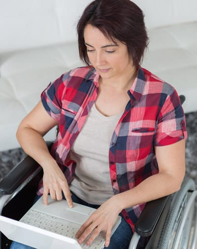 woman with disability works from home with laptop in lap in her wheelchair