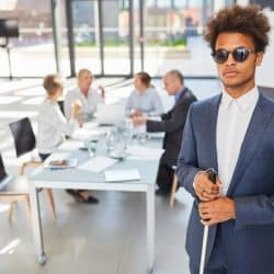 blind man holding cane in office setting and coworkers seated at conference table